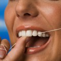 Young woman using dental floss, close-up